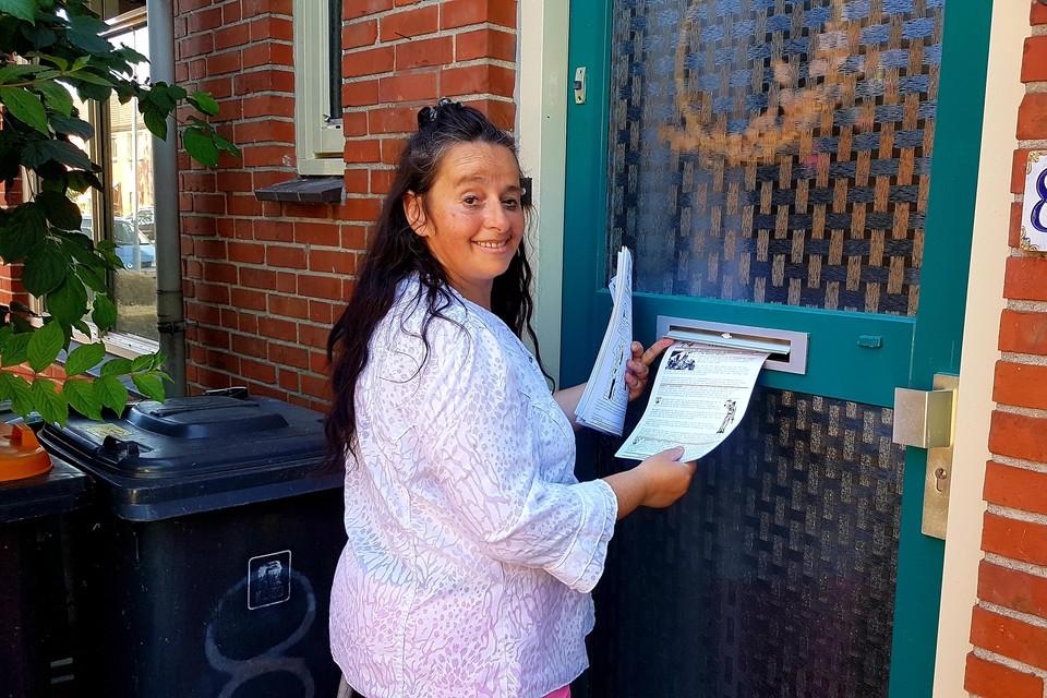 Vrijwilligster Sieka stopt de krant huis aan huis in de bus.