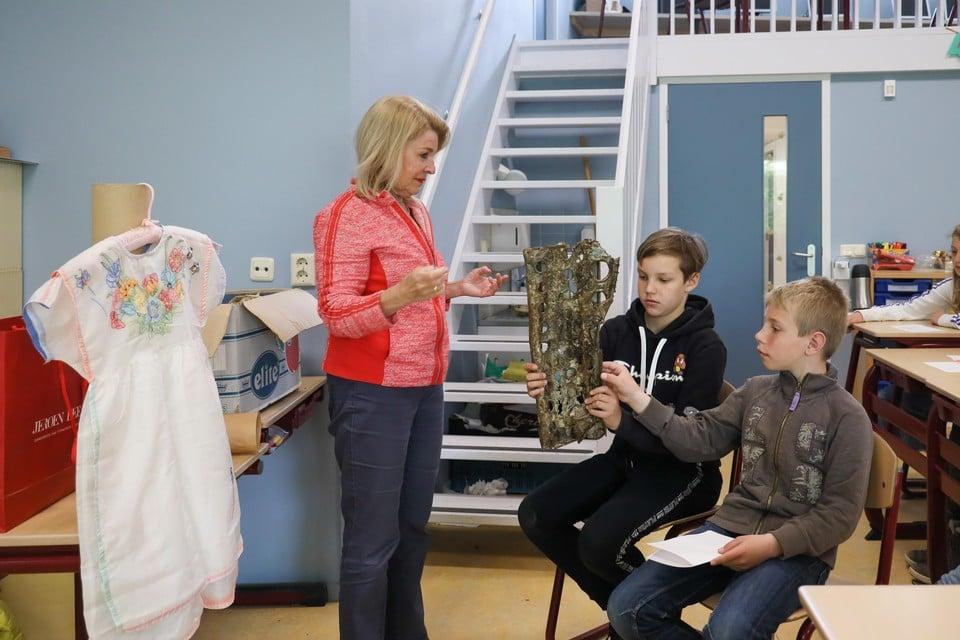Marjan Schipper-Torbijn toont de Wijdenesser leerlingen een stuk van de romp van een vliegtuig uit de oorlog. Achter haar hangt een jurk gemaakt van een oorlogsparachute.