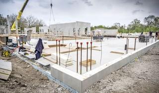 Met een hijskraan worden de loodzware wanden rechtopgezet: de eerste muren van het 'duurzaamste zwembad van de regio Alkmaar' staan