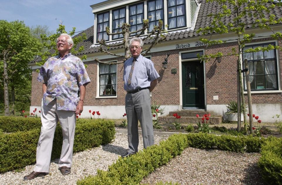 Willem Hulsegge (links) en Matthijs Porsius voor de boerderij van Zwart in Schellingwoude, waar ze aan het einde van de Tweede Wereldoorlog verbleven. ,,Met kijkers hielden we in de gaten wat er allemaal op de dijk gebeurde.''