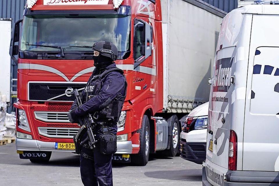 Na de inval worden grote hoeveelheden drugs in vrachtwagens afgevoerd. Een zwaarbewapende agent houdt een oogje in het zeil.