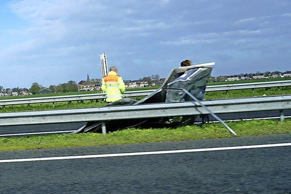 Een medewerker van Rijkswaterstaat bij het weggewaaide dak.