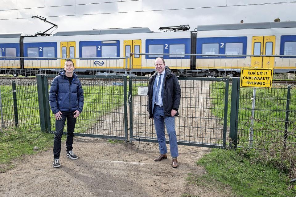 Harro Homan, regiodirecteur Prorail, en de Velsense wethouder Bram Diepstraten (rechts) sluiten de onbewaakte overweg bij boerderij Sinneveld definitief af.