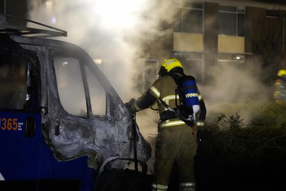 De brandweer druk bezig met het nabluswerk. Het busje van Woningstichting Den Helder raakte flink beschadigd.