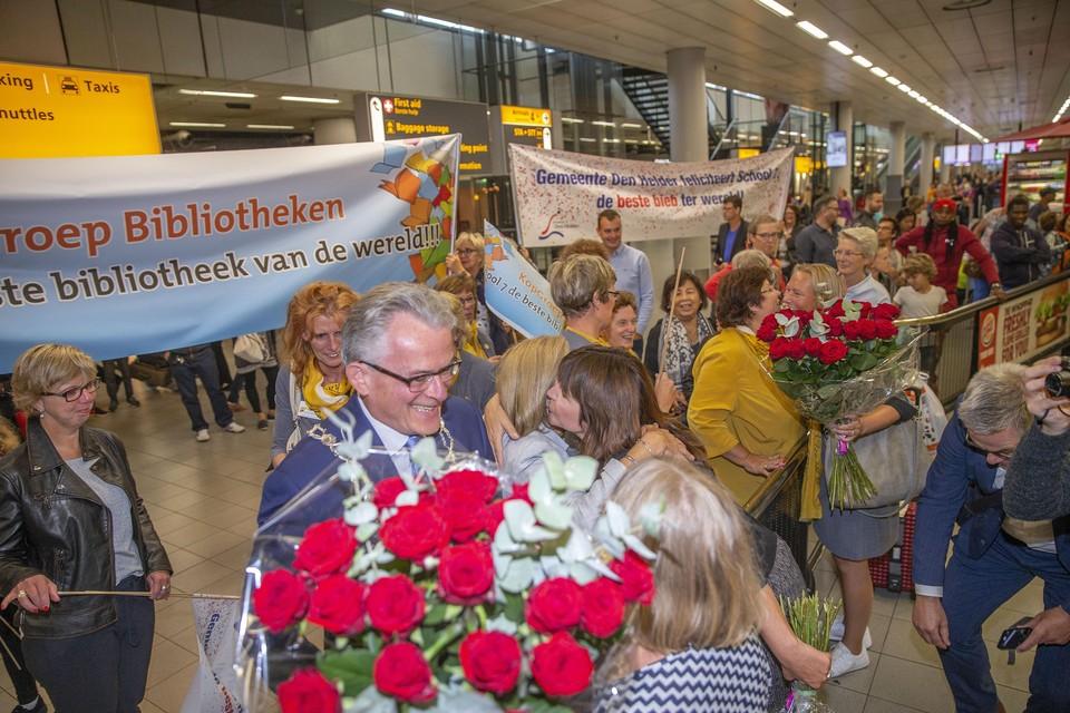 Het welkomstcomité met spandoeken en grote bossen rozen op Schiphol.