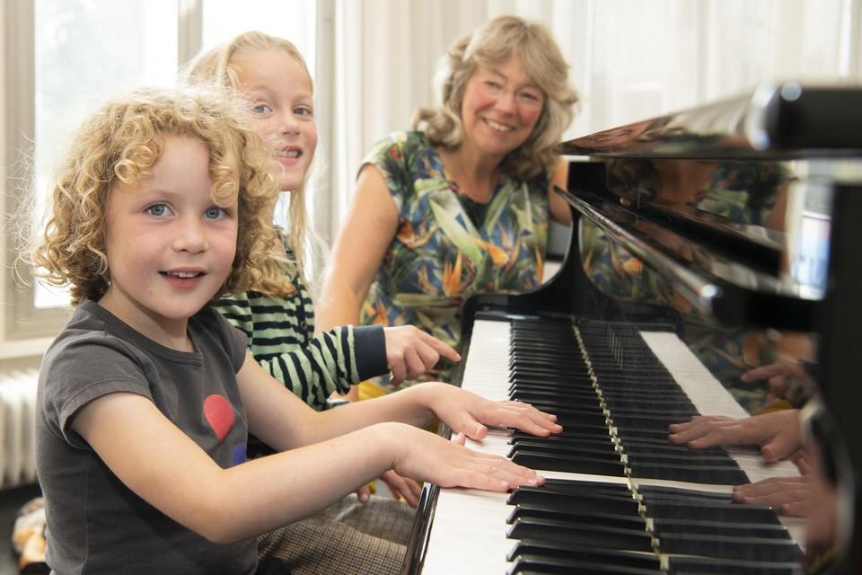 Anna en Lisa Snijders krijgen pianoles van Petra van Drieënhuizen.