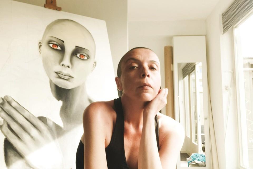 Licia Marino met op de achtergrond een van haar schilderijen.