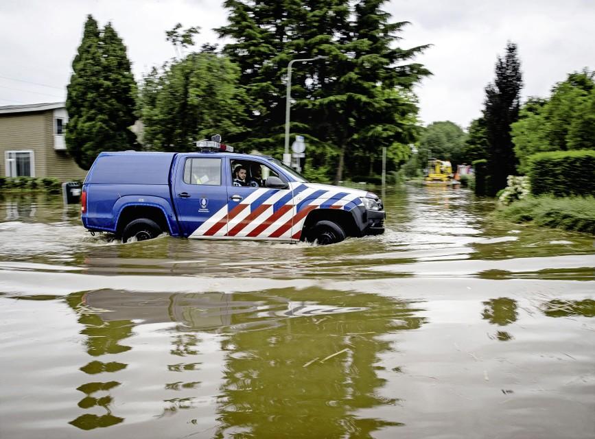 Koninklijke Marechaussee rijdt door een ondergelopen straat nadat een dijk langs het Julianakanaal is doorgebroken.