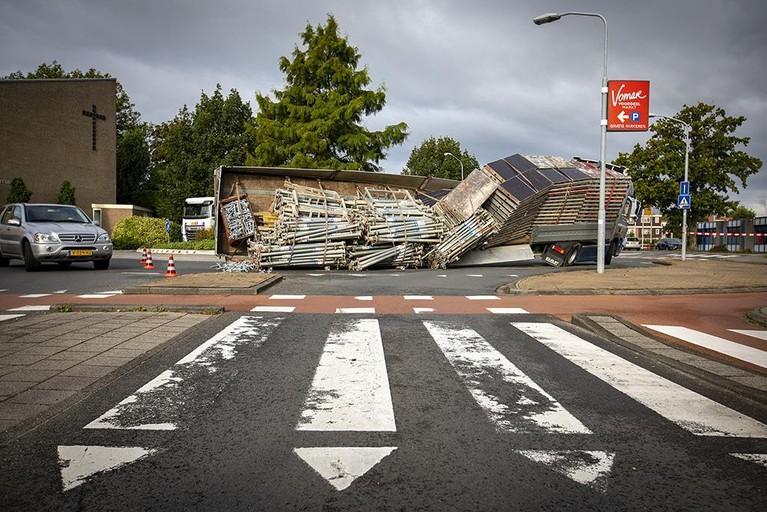 Aanhanger met steigeronderdelen gekanteld op rotonde in Haarlem