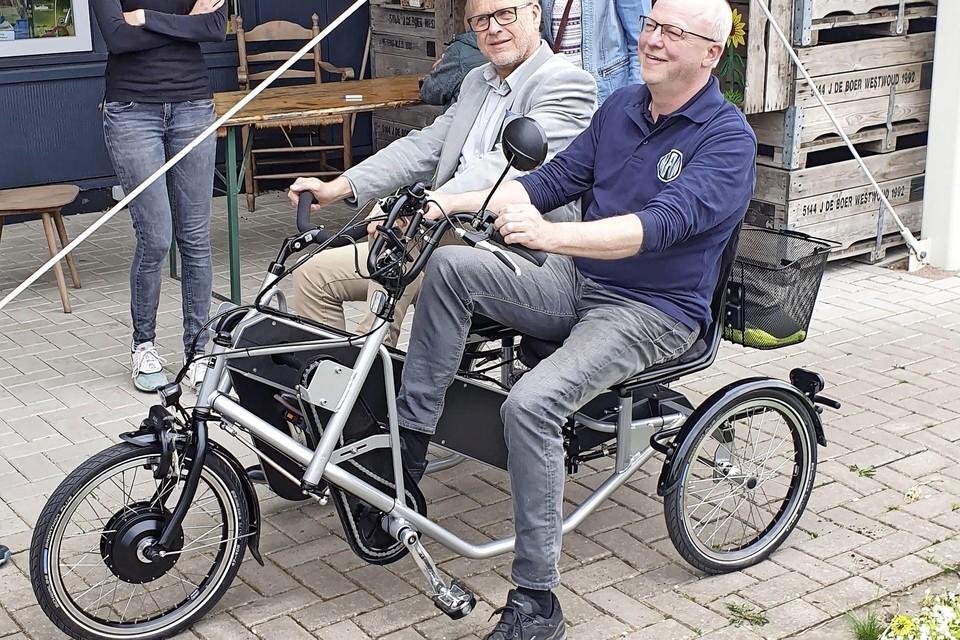 Pieter Kaij van Profile Nan en Douwe Boeijenga, secretaris van stichting De Barmhartige Fiets proberen de fiets uit. Evelien de Boer van 't Keetje en Marieke Dekker van stichting vrienden van 't Keetje kijken toe.