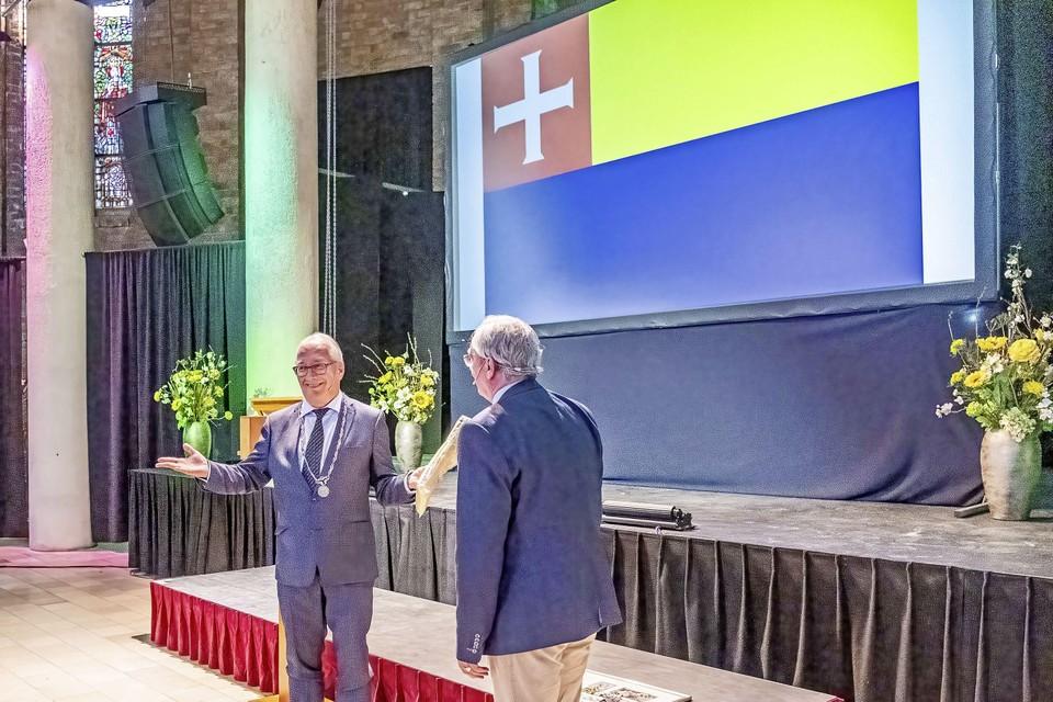 Hans Romeyn heeft in zijn linkerhand het eerste exemplaar van de vlag die hij kreeg bij zijn afscheid van raadslid Tijmen Valkering (rechts).