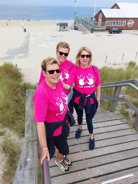 Marcella Franx, Dievera Abbekerk en Mariska Tesselaar (vlnr) op het strand, halverwege de wandeling. De tekst op hun shirt laat aan duidelijkheid niets te wensen over.