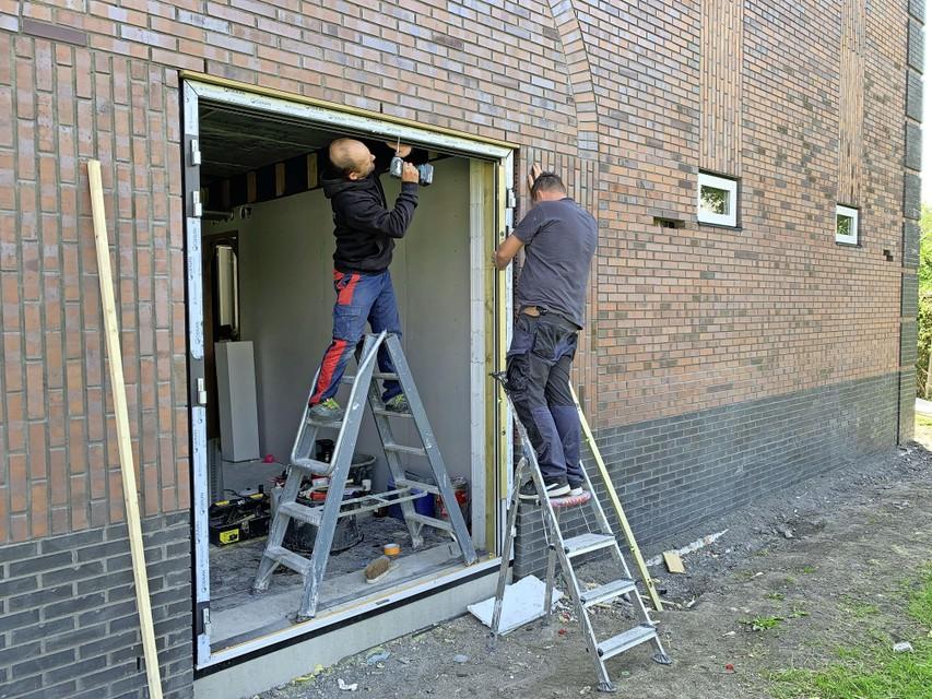 Bouwvakkers werken aan een kozijn waar straks deuren in hangen.