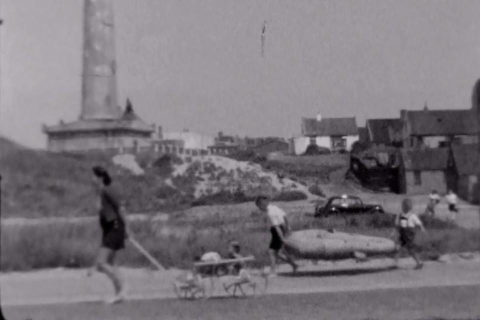 Moeder Zomerdijk met bolderwagen met dochter voorop, daarachter twee trotse broers met hun gummie-opblaasboot. In de verte de vuurtoren Van Speijk.