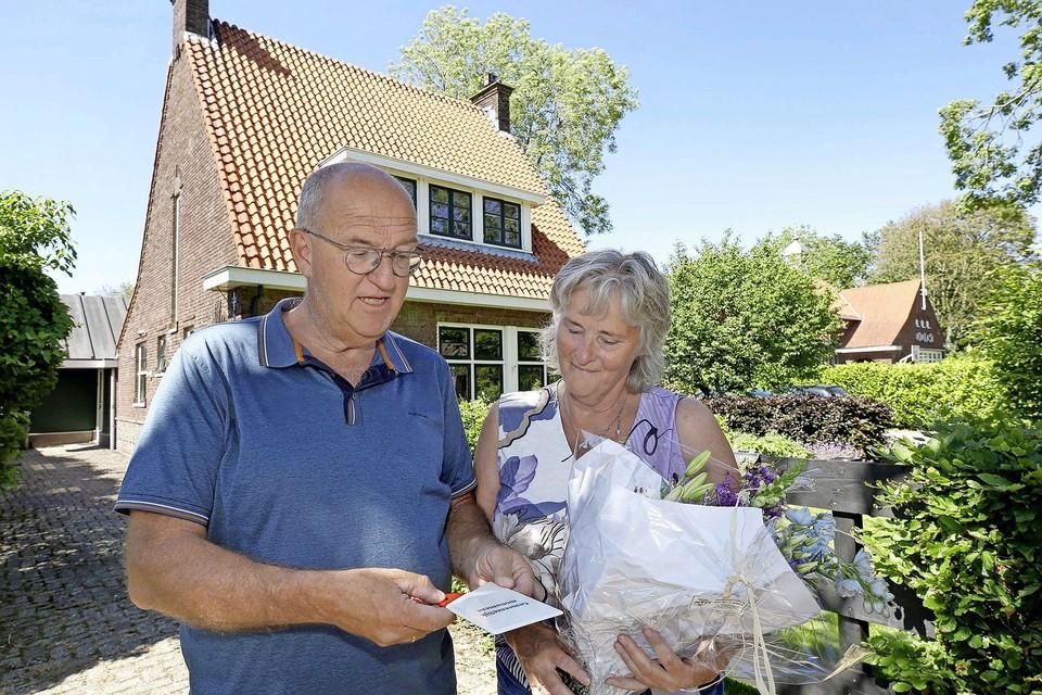 Gerald en Jannie Langerak met de ogen gericht op het zojuist ontvangen gemeentelijk monumentenschildje.