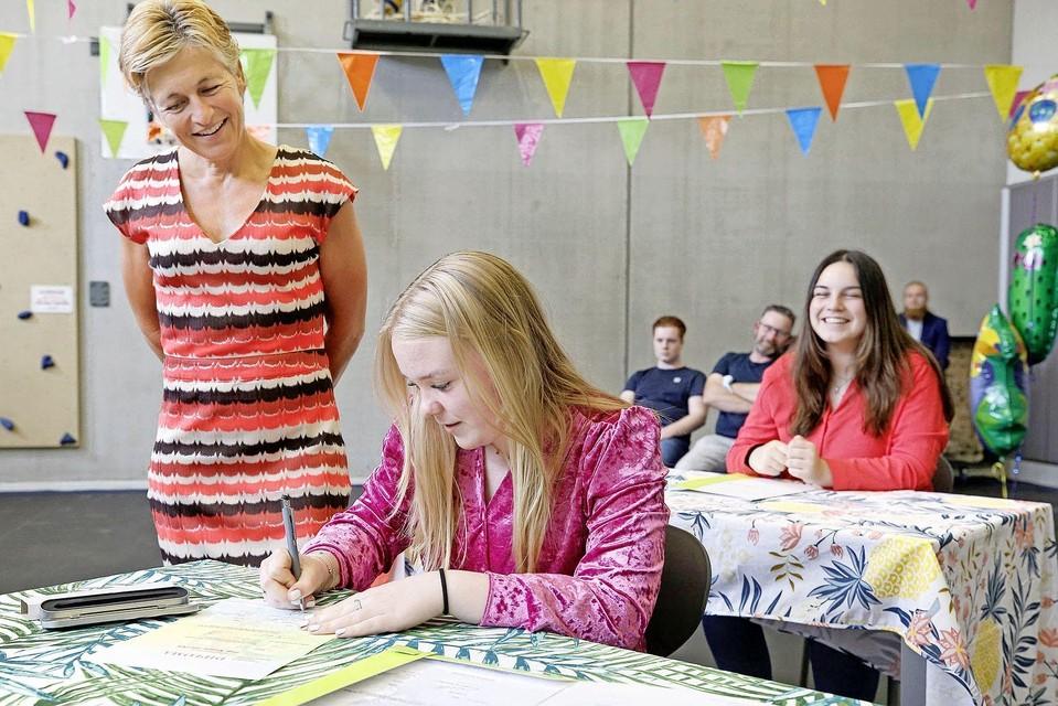 Onder toeziend oog van mentrix Betty van Dijk tekent Indy van Dok haar diploma.