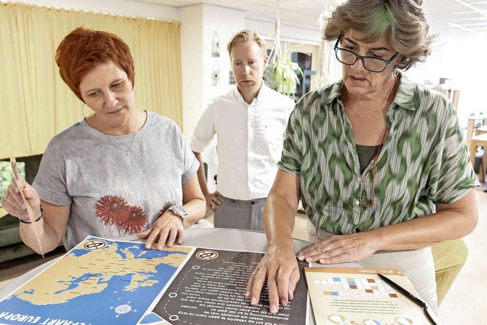 Burgemeester Marian van der Weele (rechts) en manager van De Bolder Linda Henskes proberen te ontdekken waar ze naartoe gaan op vakantie. Midden: Peter Sijpkes van Karmac Bibliotheek.