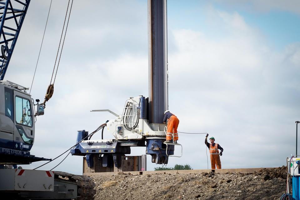 Een damwandplank wordt in de machine geplaatst die hem verder de grond induwt.