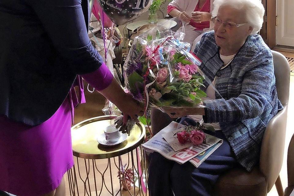 De jarige Willy van Amerongen krijgt een bos bloemen van de burgemeester.