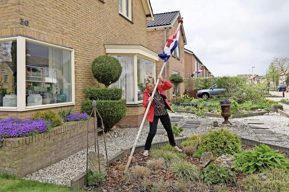 Trudie Kraakmam-Jong 'plant' de vlag bij haar woning.