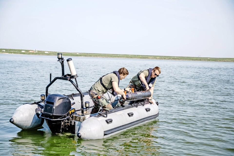 Twee zeesoldaten tillen een Remus-drone het water in.