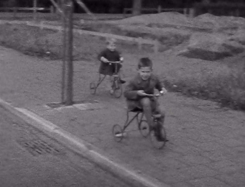 Een spannende wedstrijd tussen twee kleuters op driewielers op het trottoir. De voorste heeft een blikkie met een touwtje achter zijn racertje, en een glimmende bel op het stuur.