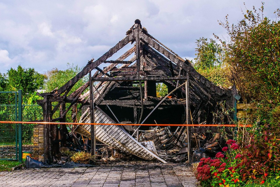 Alleen zwartgeblakerd geraamte met dakresten herinnert aan de schuur die er voor de brand stond.
