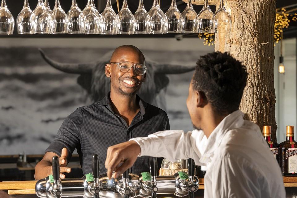 Restauranteigenaar Clifton Tuinfort was blij dat barman Favour Ijesuorobo (in verband met zijn veiligheid staat zijn gezicht niet op de foto) kon beginnen. Nu wordt de 23-jarige Nigeriaan het land uitgezet.