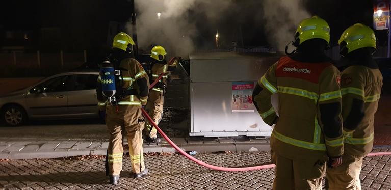 Brandende container volgepompt met water in Obdam