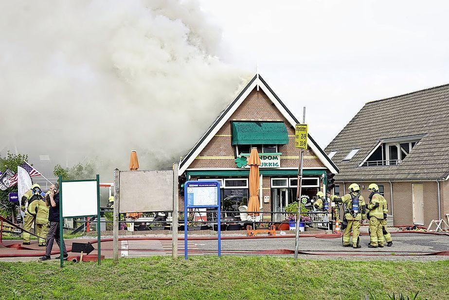 Brandweerliden buigen zich over de vraag hoe ze de brand het best kunnen bestrijden.