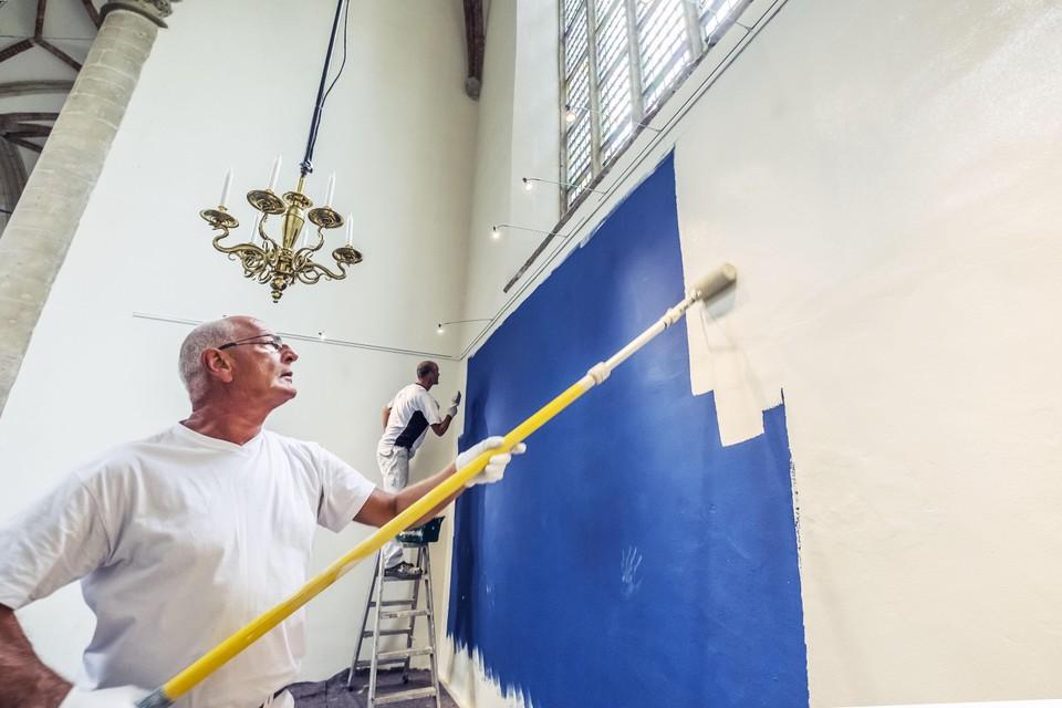 Henk Delis (links) en Remco Smit van het Alkmaarse schilderbedrijf Smit en Smit gaan met verfroller en kwast over de gekleurde wanden heen.