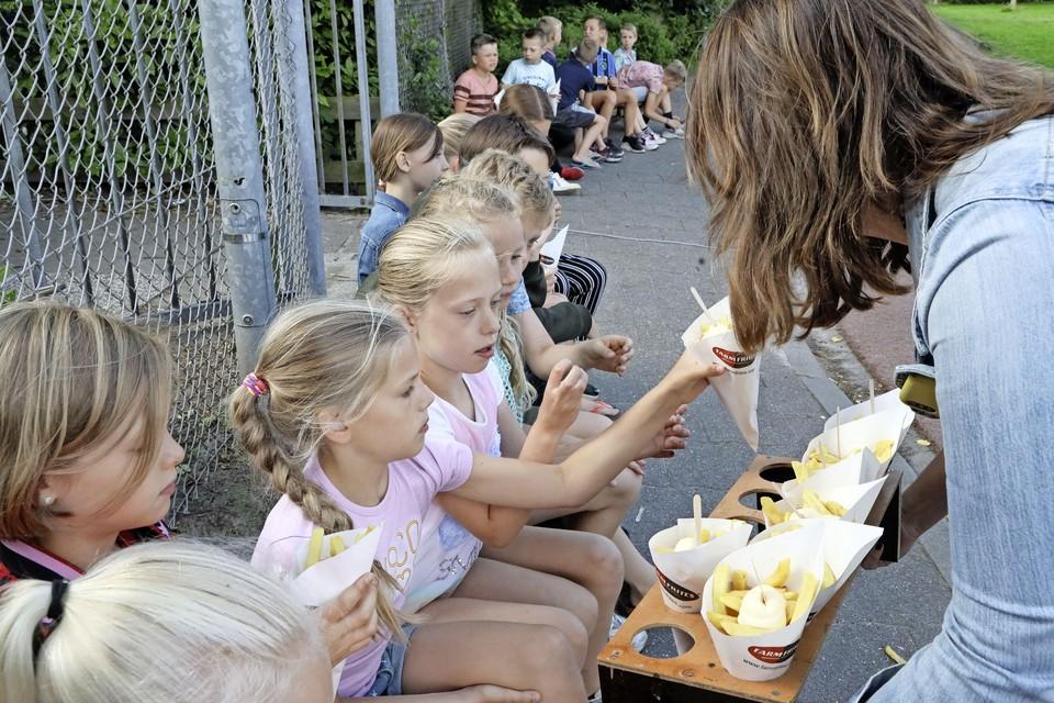 De kinderen laten de patat zich goed smaken.