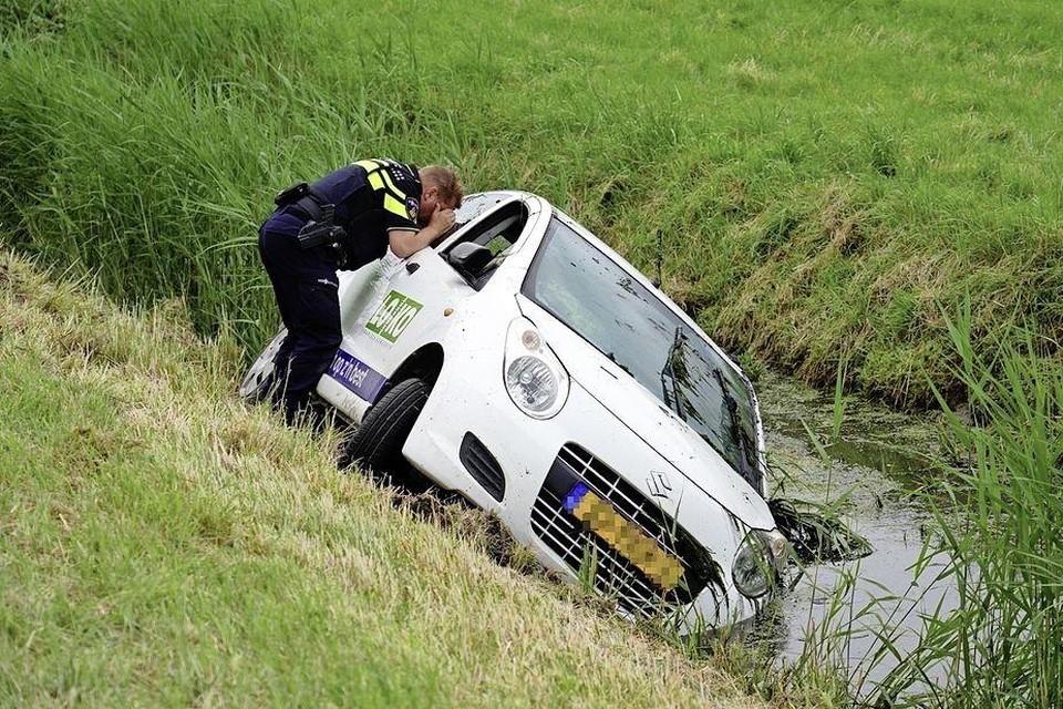Een agent controleert de binnenkant van de auto.