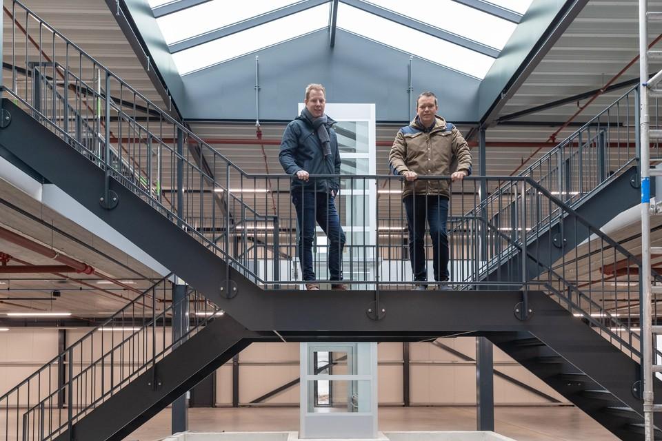 Jan Willem Algra (l) en Marc Takken op de trap boven de vijver, met achter hen de doorzichtige lift.