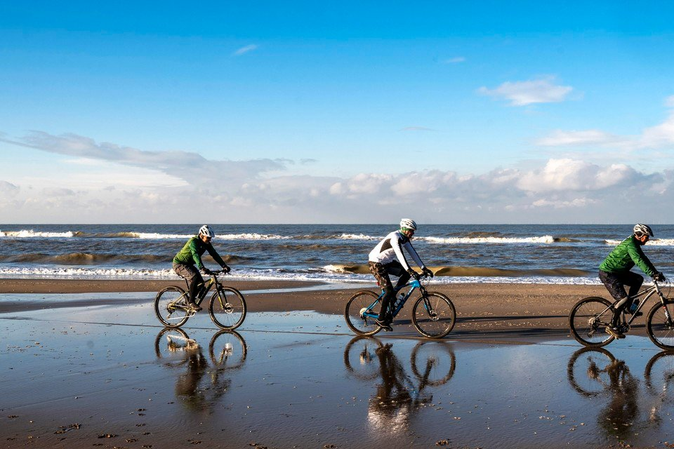 Mountainbikers (staart naar kop) Guy Dersigni, Johan van Marle en Kees Reinders op het strand van Bloemendaal.