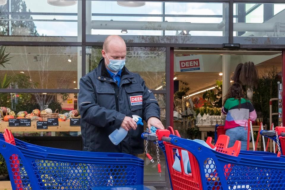 Een medewerker van Deen in de Vredehofstraat in Hoorn reinigt de winkelwagens om nieuwe coronabesmettingen tegen te gaan.