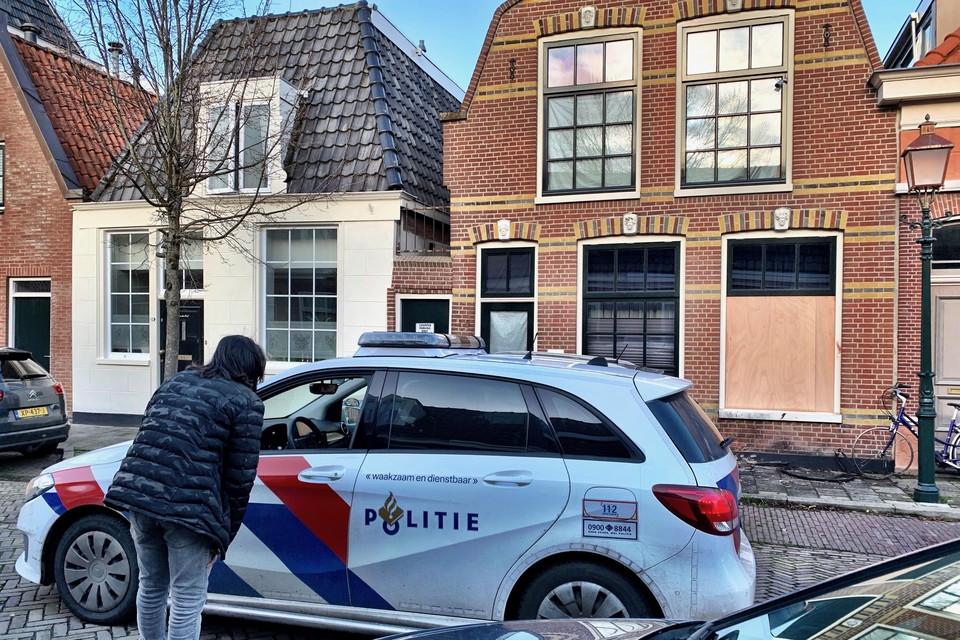 De bewoner praat met de politie, op de achtergrond het getroffen huis.
