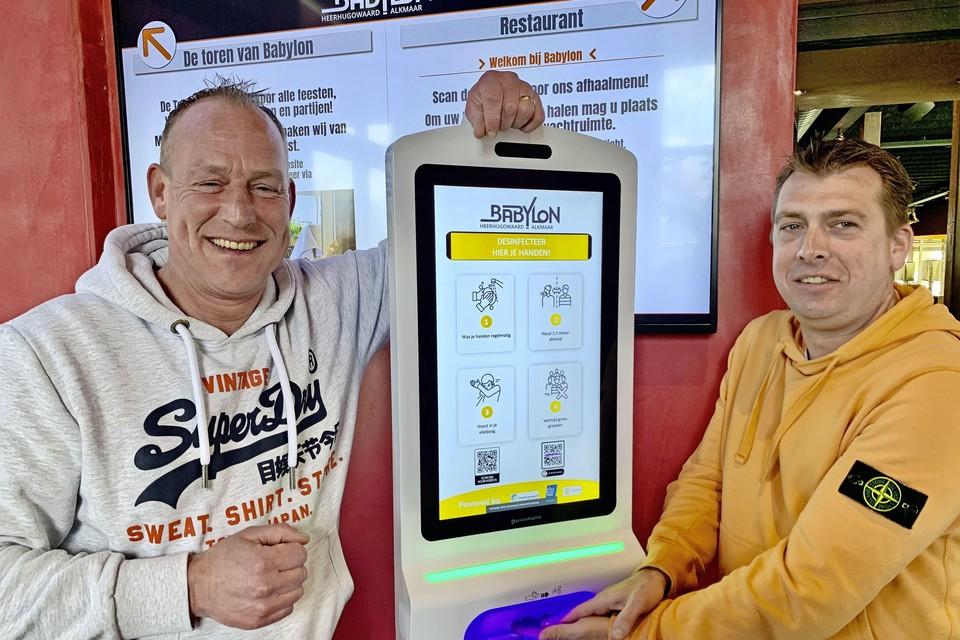 Horecaondernemers Mike Karels (links) en Rik Jonk zijn blij met de desinfectiezuil.
