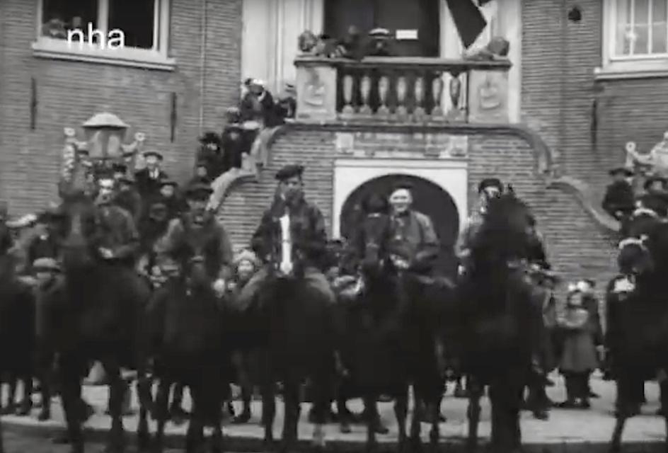 Erewacht te paard bij het stadhuis, waar ook padvinders staan opgesteld.