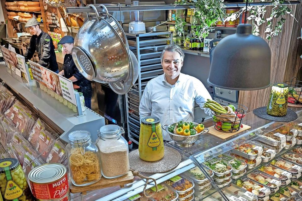 Serdar Tolenaar in zijn Plus-supermarkt  met op de voorgrond in het schap Mama's Maaltijden. Achter Tolenaar de keuken waarin het allemaal begon.