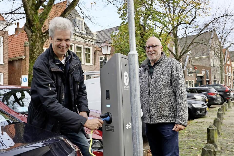 Alex Bezemer (rechts) en René van Ophem van de projectgroep elektrische deelauto bij een bestaande laadpaal in Hoorn.