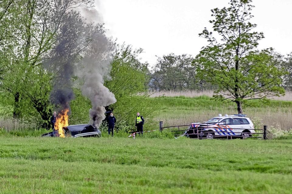 Een van de in brand gestoken vluchtauto's.