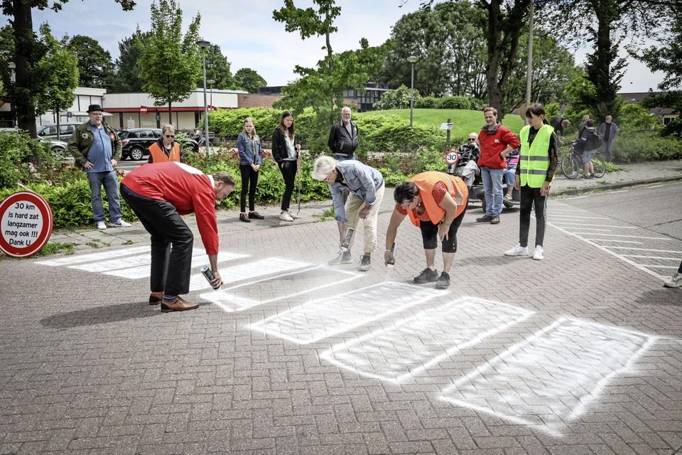 Bewoners van de Overstort in Grootebroek spuiten zelf een zebrapad op hun straat.