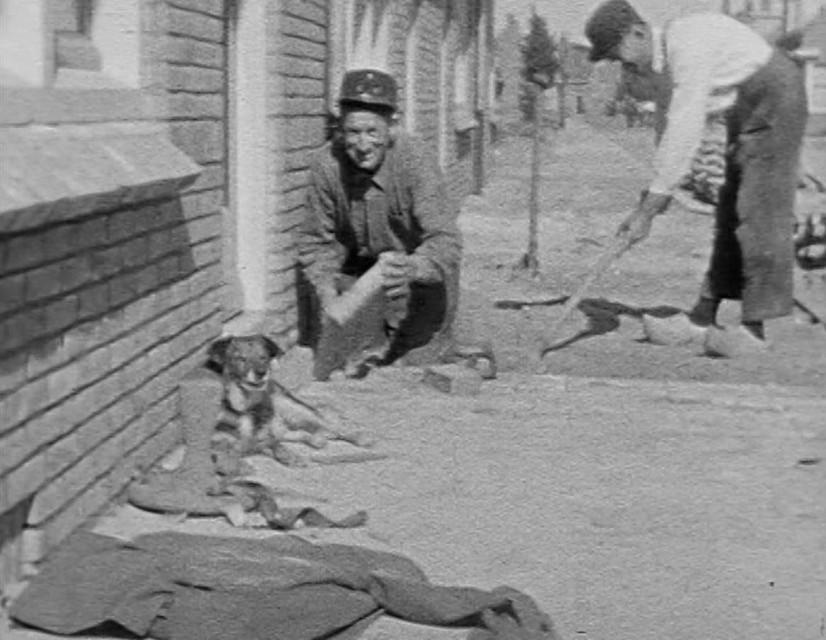 Lachend kijkt één van de stratenmakers in de lens van de camera, de ander concentreert zich meer op het werk. Een oud hondje ligt heel rustig tegen de muur te genieten van de zon.