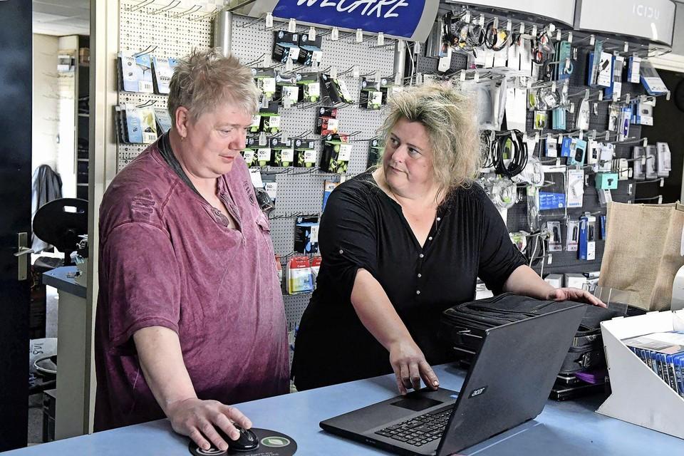 Jacco en Coby Wiersma met een laptop aan de toonbank van hun winkel in Den Oever. ,,Had de gemeente maar een mailtje gestuurd, dan hadden wij ook mee kunnen dingen.''
