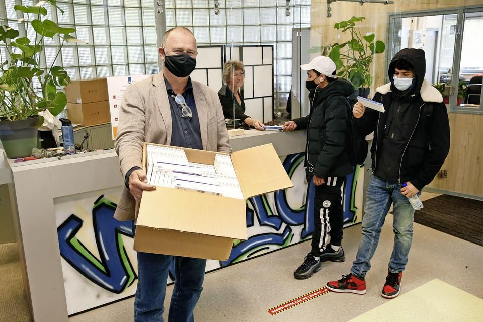 Kees Versteeg (rector van het Griftland College) met een doos coronazelftests; leerlingen kunnen ze op school afhalen om thuis te testen.