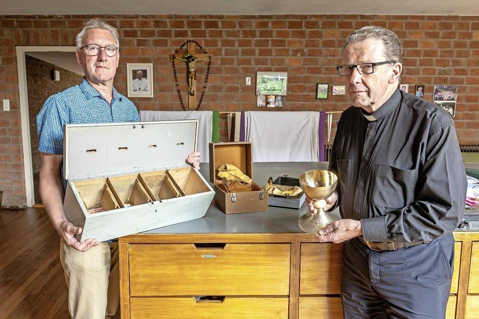 Koster Hennie Buijs met een doos waarin kelken bewaard worden en pastoor Paul Stomph toont een kelk.