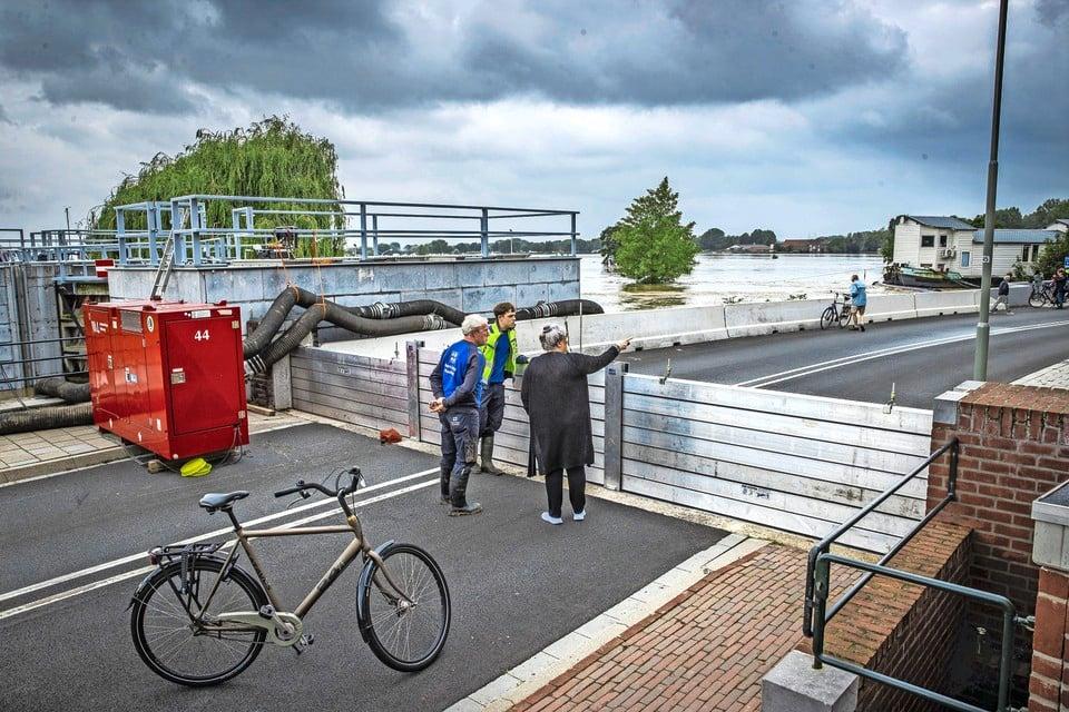 Mensen staan te kijken naar het hoge water bij een gesloten coupure waar de Roer in de Maas stroomt in het centrum van Roermond.