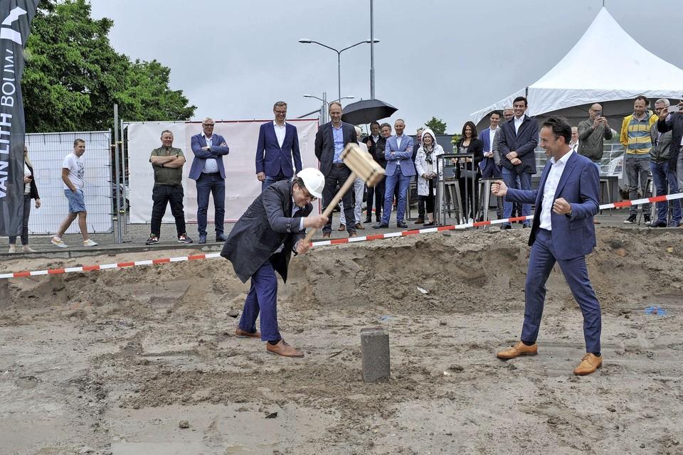 Onder toeziende oog van projectontwikkelaar Bart de Jong helpt wethouder Serge Ferraro helpt de bouwers met het slaan van de eerste paal.