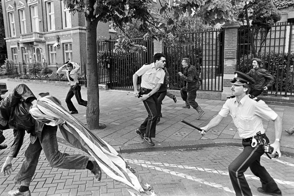 In augustus 1983 maakte Bert Verhoeff deze foto van een actie tegen kruisrakettenbij het Amerikaanse consulaat in Amsterdam. Politieagenten en actievoerders zijn verwikkeld in een veldslag. Tóch roept de foto een glimlach op. Verhoeff: ,,Als een regisseur een scène over een confrontatie tussen agenten en demonstranten zou filmen, zou het er zó uit zien. Overal gebeurt wat. Een agent is met de hand op zijn pistoolholster klaar om zijn wapen te grijpen en een andere agent achtervolgt met wapenstok en portofoon een struikelende demonstrant die de Amerikaanse vlag heeft bemachtigd. De derde agent zet zijn pet recht en twee andere demonstranten schreeuwen een oorlogskreet.''